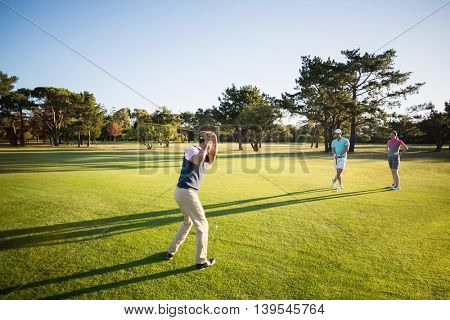 Full length of people playing golf while standing on field