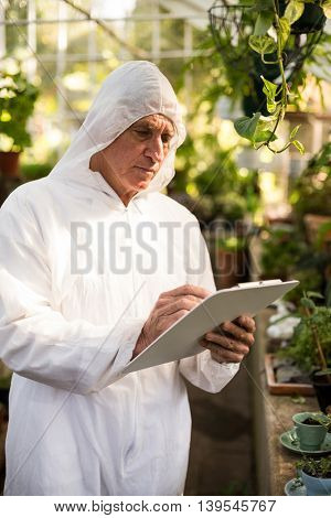 Male scientist writing on clipboard while examining plants at greenhouse