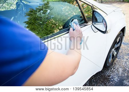 Back View Of Man Washing Car With Microfiber Cloth
