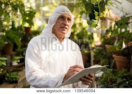 Male scientist writing on clipboard while inspecting in greenhouse