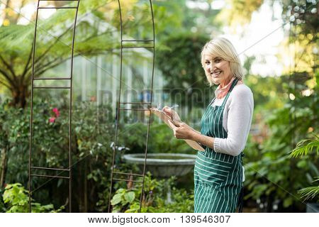 Portrait of woman smiling while writing in clipboard outside greenhouse