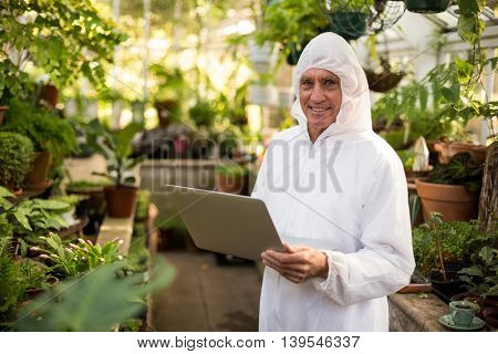 Portrait of happy male scientist using laptop at greenhouse
