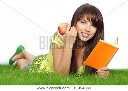 Young beautiful woman lays on green field and reads book.
