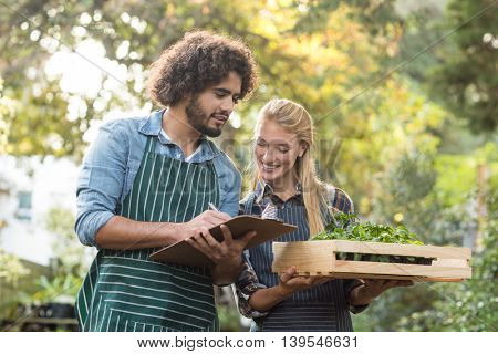 Man writing on clipboard while female gardener holding plants in crate outside greenhouse