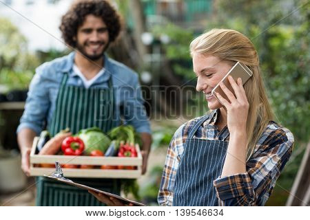 Happy female gardener talking on cellphone while man standing with vegetable crate in background