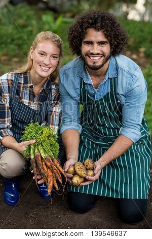 Portrait of happy male and female gardeners holding harvested carrots and potatoes on field