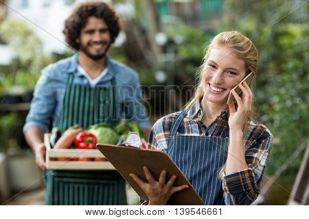 Portrait of female gardener talking on mobile phone while man standing with vegetable crate in background