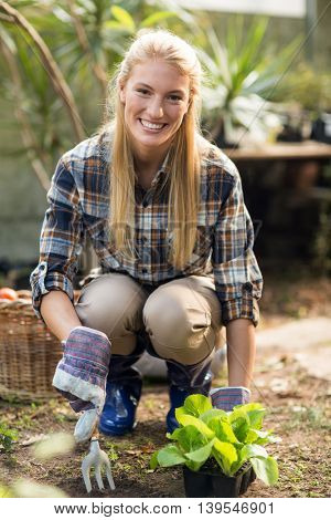 Portrait of confident female gardener smiling while planting outside greenhouse