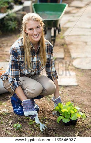 Portrait of happy female gardener planting outside greenhouse