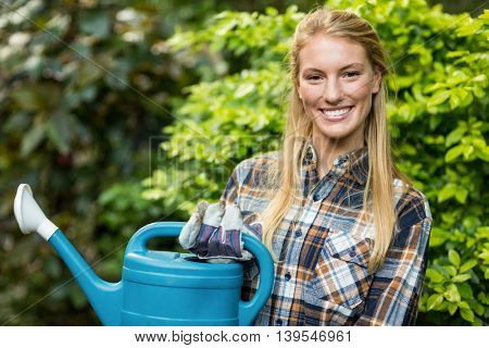 Portrait of confident female gardener holding watering can while standing at greenhouse
