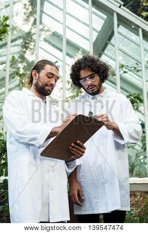 Low angle view of male scientists discussing over clipboard outside greenhouse