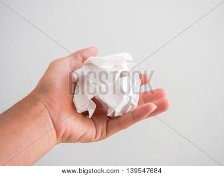 Isolated hand holding a white paper ball