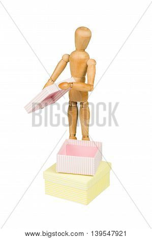 Wooden mannequin opens little box isolated on white.