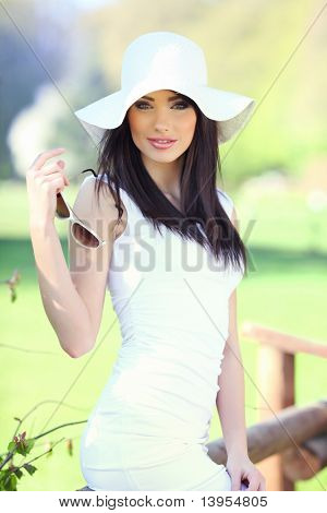 Glamour portrait of a beautiful young woman in summer park.
