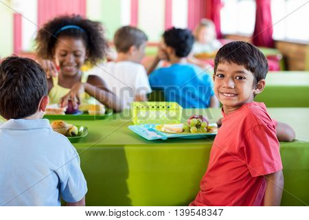 Portrait of cute boy with classmates having meal in canteen