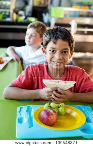 Portrait of happy boy with classmates having meal in canteen
