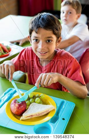 Portrait of smiling boy with classmates having meal in canteen