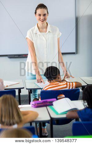 Portrait of confident female teacher teaching children in classroom