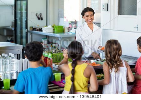 Happy woman serving food to schoolchildren in canteen