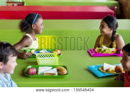 Happy schoolchildren having breakfast in canteen