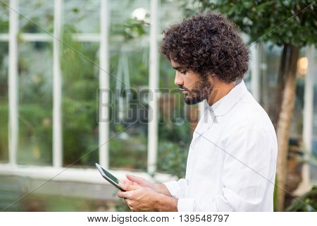 Side view of male scientist using digital tablet outside greenhouse