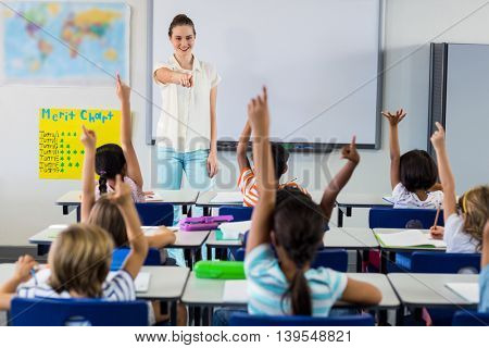 Smiling female teacher pointing students with raised hands in classroom