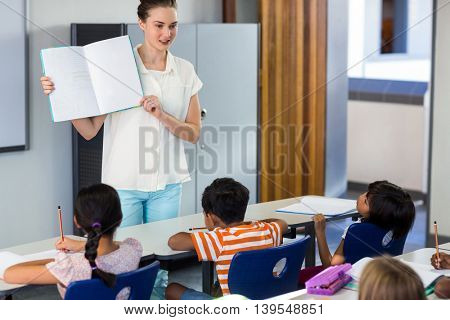 Female teacher showing book with children in classroom