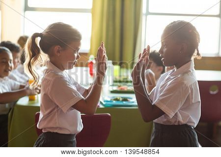 Girls playing clapping game in school canteen