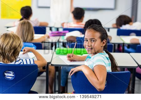 Portrait of smiling girl with classmates in classroom
