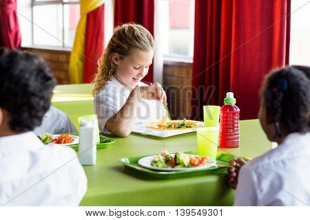 Smiling schoolgirl having food with classmates in canteen