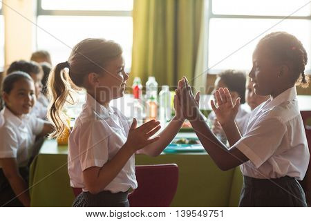Smiling schoolgirls playing clapping game in canteen