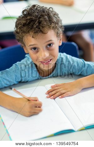 Portrait of smiling boy writing on book in classroom