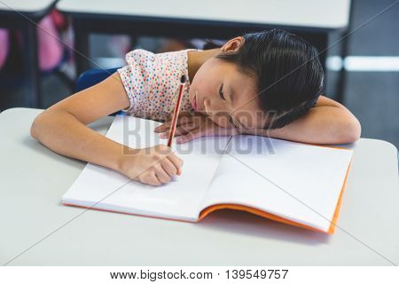 Thoughtful schoolgirl with book in classroom