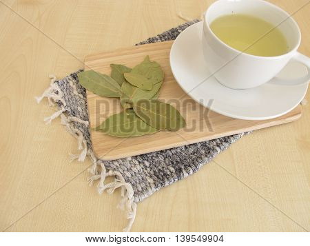 Cup of bay leaves tea and dried bay leaves