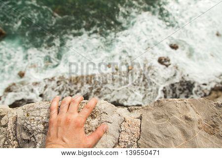 Man standing on the edge of cliff, holding with one hand and watching down.
