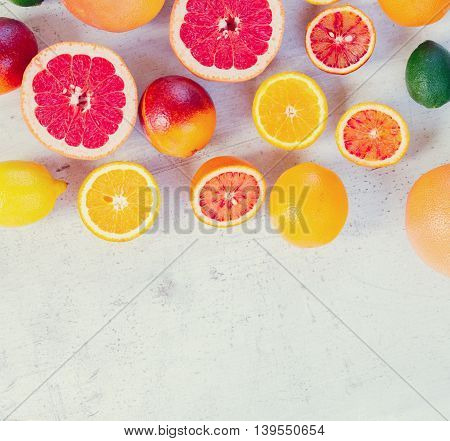 Variety of whole an cut citruses with copy space on white wooden table, retro toned