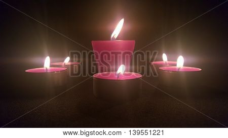 Beautiful candles burning on a black material