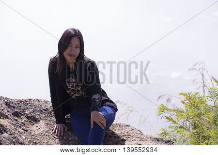 Thai woman with backpack sitting on cliff