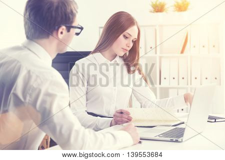 Businessman sitting next to businesswoman who is looking through notes office at background. Concept of cooperation. toning filter