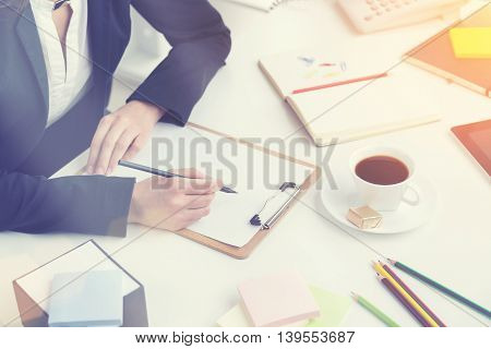 Businesswoman sitting at table and making notes. Notebook and cup in front of her. Only hands seen. Office. Concept of work.toning filter
