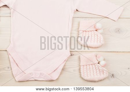 Closeup of baby girl bodysuit and socks on light wooden table. Top view Mock up