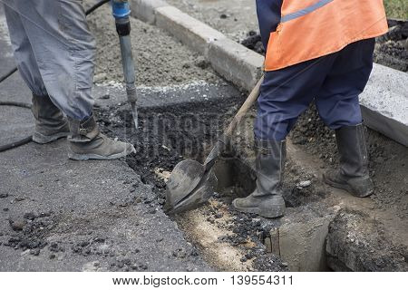 Road Paving Construction. Workers laying stone mastic asphalt during street repairing works. Worker making asphalt with coated chippings. Drainage repair installation of manhole