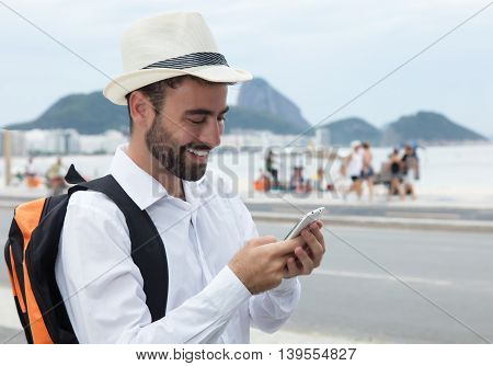 Laughing tourist looking for the right way at phone outdoor at Rio