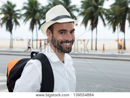 Tourist with backpack looking at camera outdoor in the summer