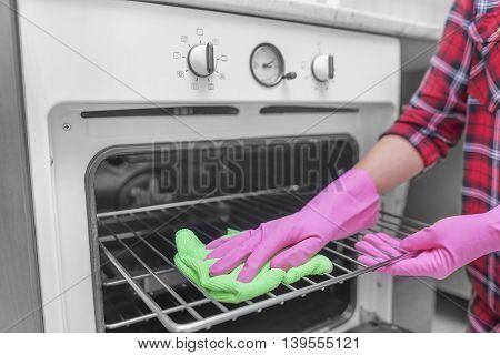Women washed gloved hands inside oven. Close-up.