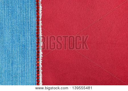 Denim decorated with red rhinestones lying on red satin with space for text