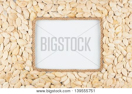 Frame made of rope with pumpkin seeds and a white background with space for your text