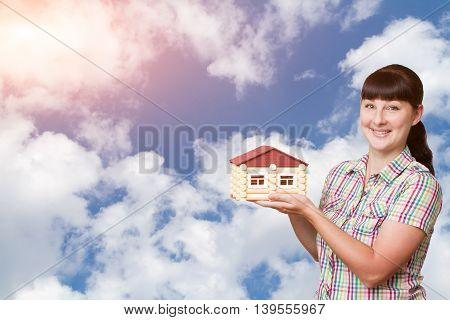 Young woman holding home isolated on a background of sky and clouds.