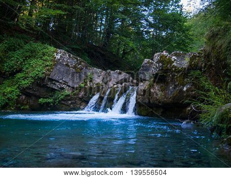 Small beautiful blue waterfall with very clear water
