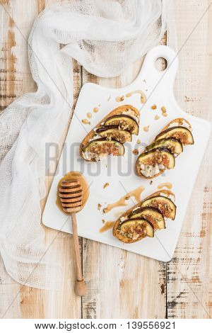 Swedish toasts with figs cheese rosemary honey and walnuts on a cutting board. Top view